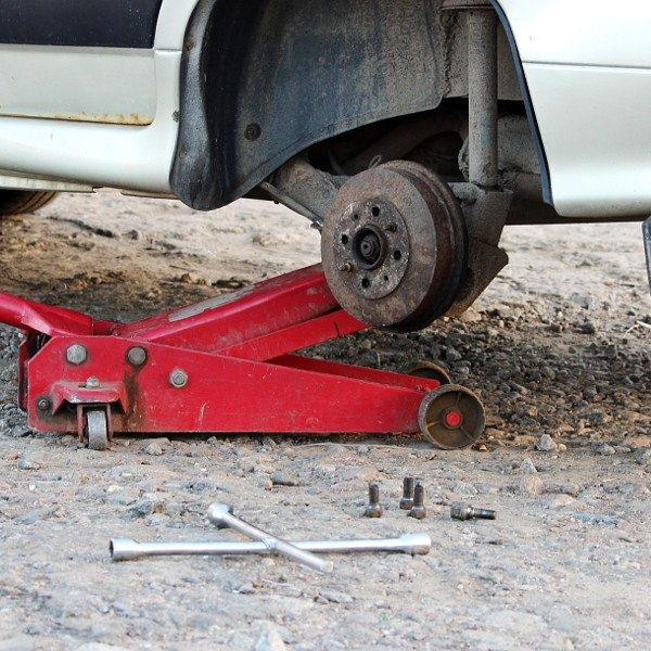 Car fixed in the garage, Hydraulic floor jack lift a , Wheel without tire, Key cross road and...