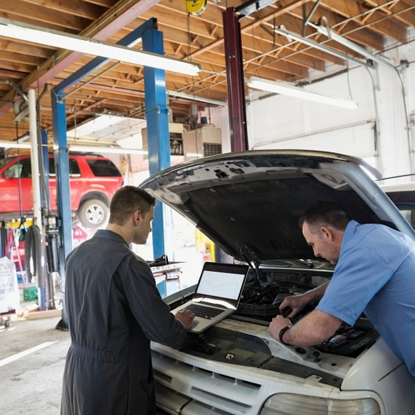 Mechanics with laptop performing engine diagnostics