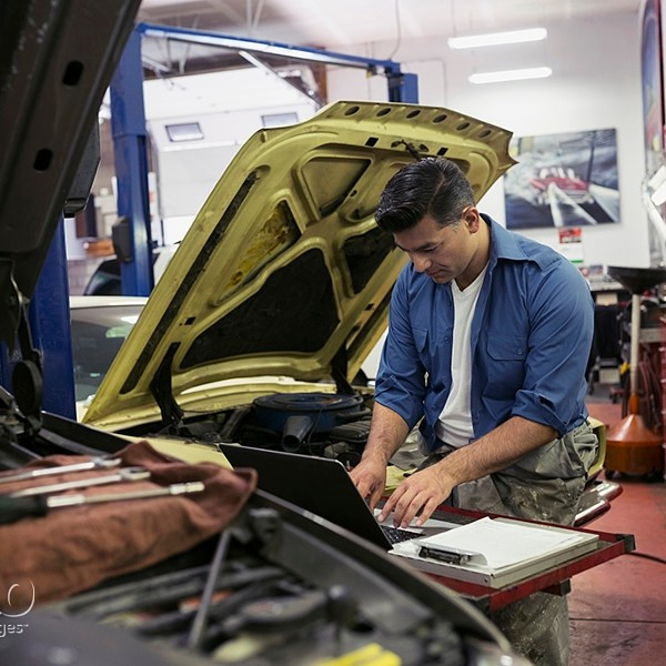 Mechanic diagnostic testing at laptop auto repair shop