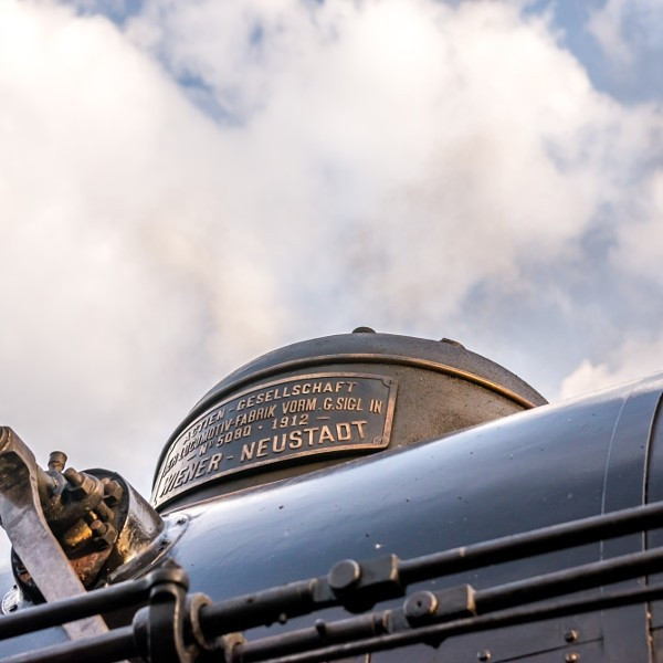 Closeup view of a sand dome on top of steam locomotive boiler against the background of clouds on...