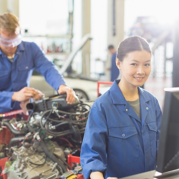 Portrait smiling female mechanic at computer in auto repair shop