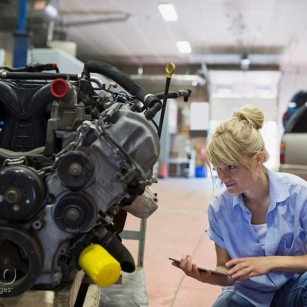 Female mechanic with digital tablet examining engine