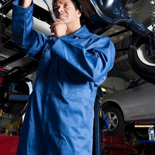 Middle Eastern mechanic working on car