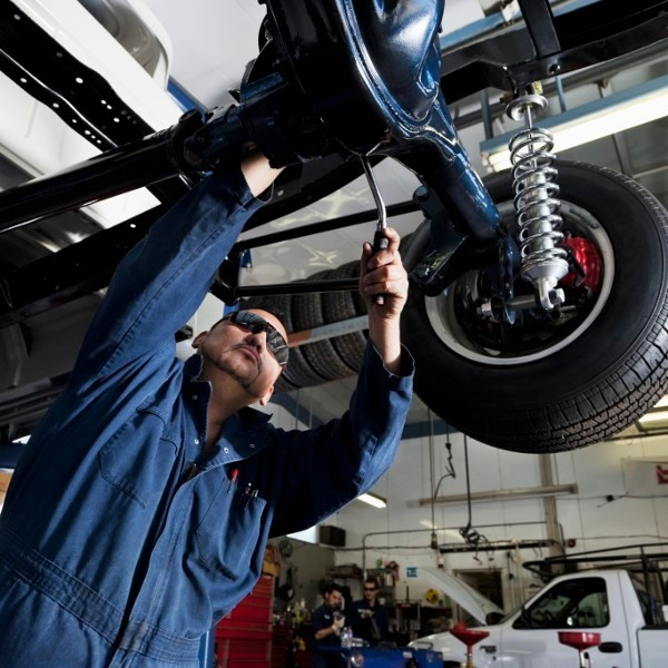 Hispanic mechanic working on car