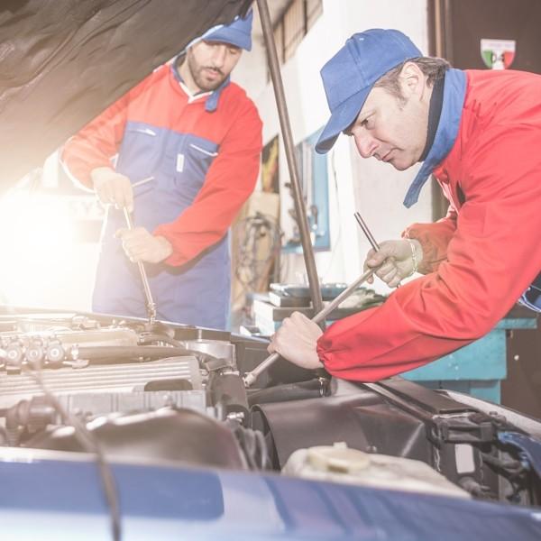 Two mechanics working on a car