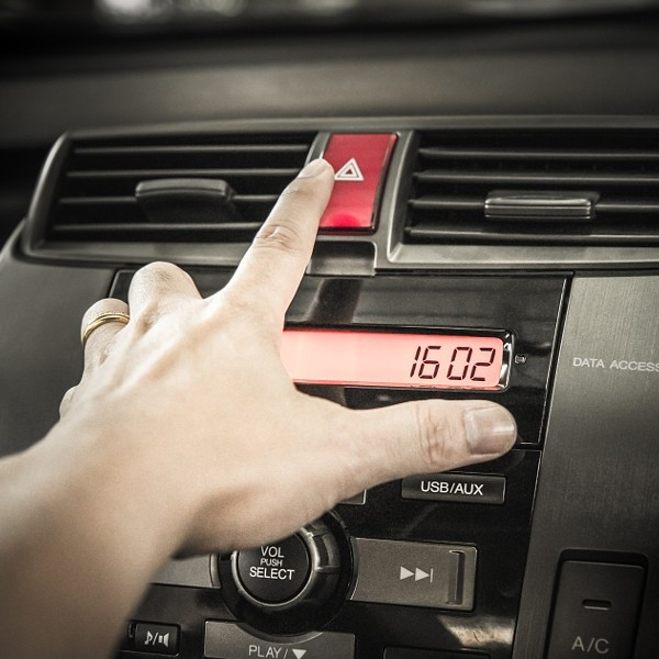 Closeup of young man pressing emergency button on car sport dash