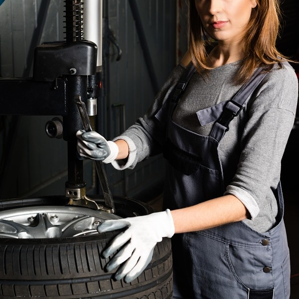 Young trainee changing car tyre