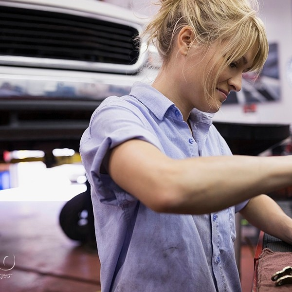 Female mechanic fixing part in auto repair shop