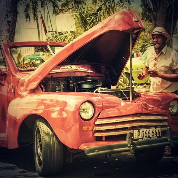 Cuban repairing his old american car