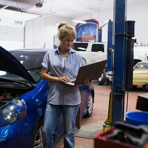 Female mechanic using laptop in auto repair shop