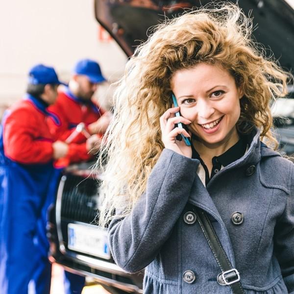 Woman calling car assistance service after car break down