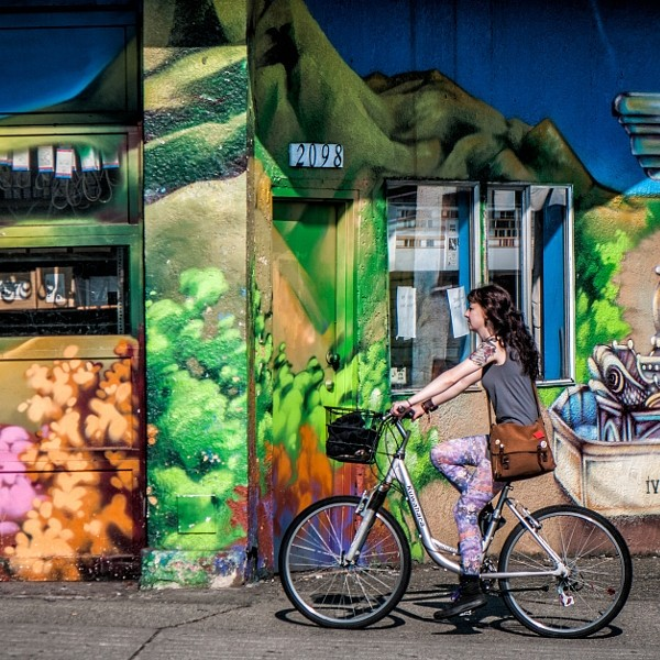 Girl riding on her bike, Commercial Drive, Vancouver BC
