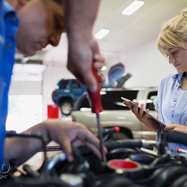 Female mechanic with digital tablet fixing engine